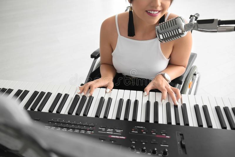 Mooie jonge musicus in rolstoel het spelen synthesizer en thuis het zingen royalty-vrije stock fotografie