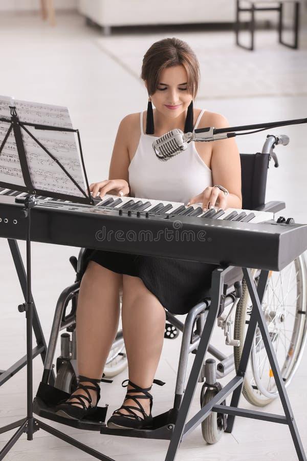 Mooie jonge musicus in rolstoel het spelen synthesizer thuis royalty-vrije stock fotografie