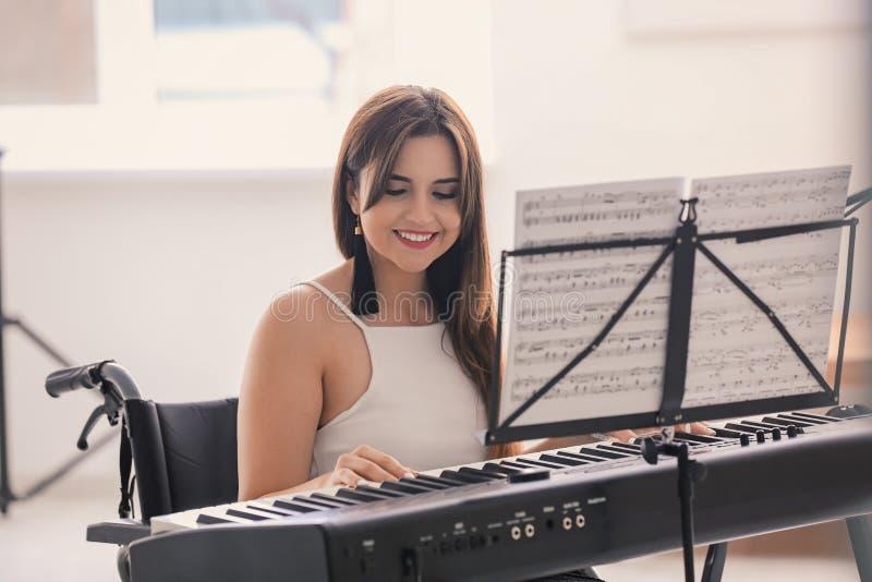 Mooie jonge musicus in rolstoel het spelen synthesizer thuis royalty-vrije stock foto