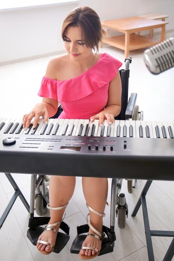 Mooie jonge musicus in rolstoel het spelen synthesizer thuis royalty-vrije stock afbeelding
