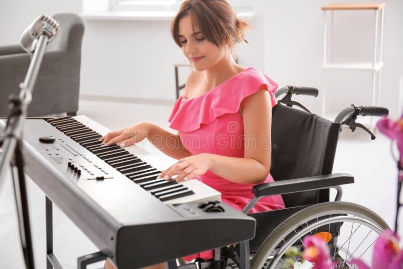 Mooie jonge musicus in rolstoel het spelen synthesizer thuis royalty-vrije stock afbeeldingen