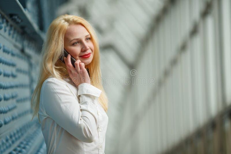 Mooie jonge onderneemster die bij mobiele telefoon en het glimlachen spreken stock foto