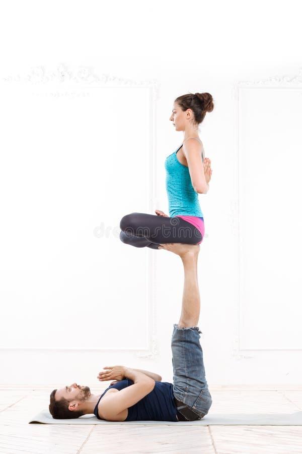 Mooie Jonge Paar het Praktizeren acro-Yoga stock foto
