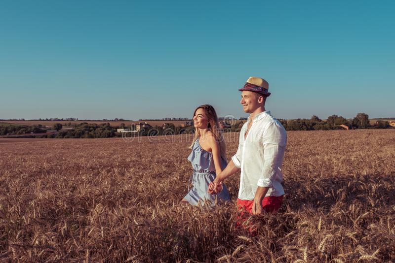 Mooie jonge paar, man en vrouw, het lopen tarwegebied in zomer, die elkaars hand, gelukkig glimlachen de houden romantisch royalty-vrije stock afbeelding