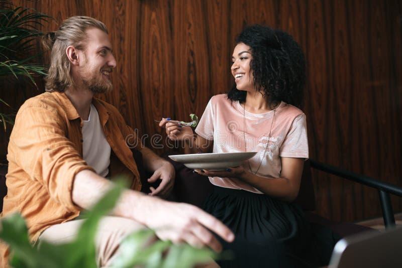 Mooie jonge paar zitting en gelukkig het spreken in restaurant Vrij Afrikaanse Amerikaanse damezitting in koffie met royalty-vrije stock foto