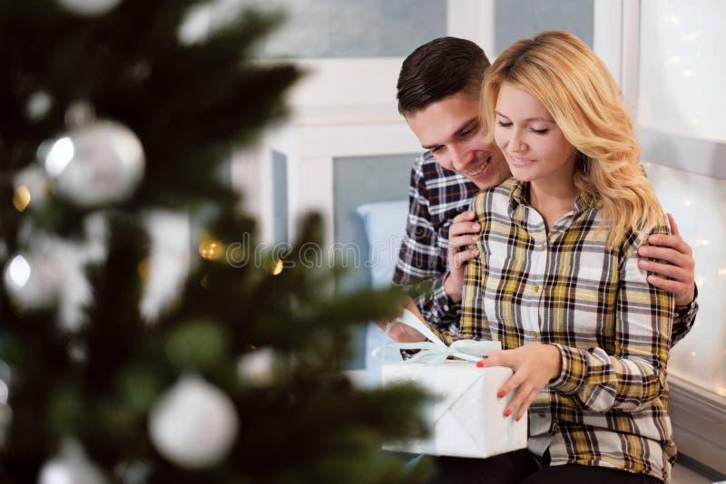 Mooie jonge paarzitting door het venster met Nieuwjaar` s decoratie en Kerstboom royalty-vrije stock foto's