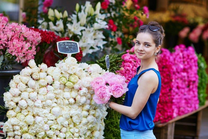 Mooie jonge Parijse vrouw die roze pioenen selecteren royalty-vrije stock afbeeldingen