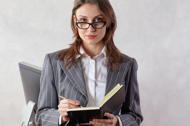 Mooie jonge professionele donkerbruine vrouw in bureau met oogglazen, die in een stootkussen, met zekere uitdrukking schrijven royalty-vrije stock afbeeldingen