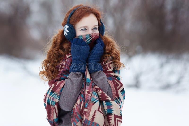 Mooie jonge roodharige vrouw in blauwe hoofdtelefoons en grote etnische sjaal stock fotografie