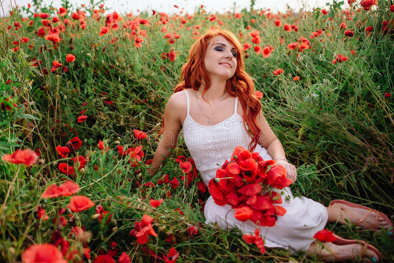 Mooie jonge roodharige vrouw op papavergebied die een boeket van papavers houden royalty-vrije stock afbeeldingen