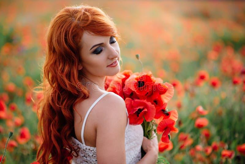 Mooie jonge roodharige vrouw op papavergebied die een boeket van papavers houden stock foto's