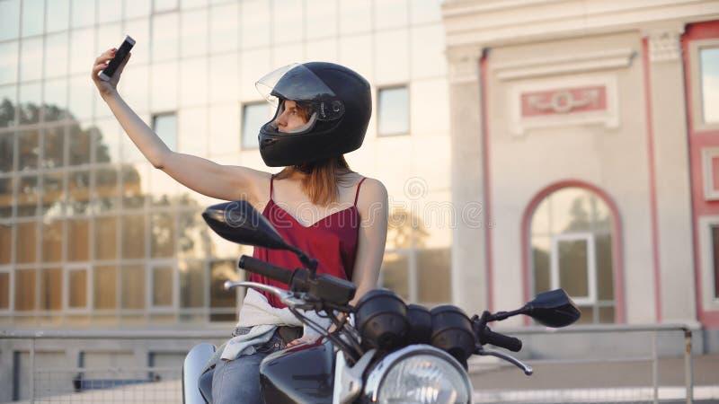 Mooie jonge roodharige vrouwenmotorrijder met zwarte motorfietshelm stock foto's