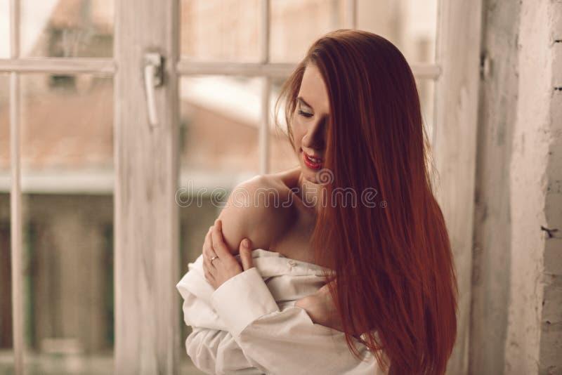 Mooie jonge roodharigevrouw met lange haarzitting op windowsil royalty-vrije stock afbeeldingen