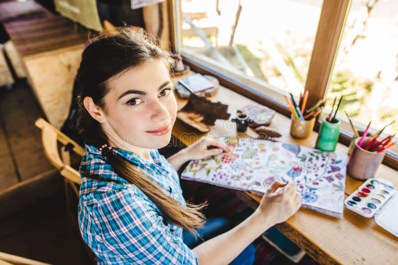 Mooie jonge schilder in haar studio stock foto's
