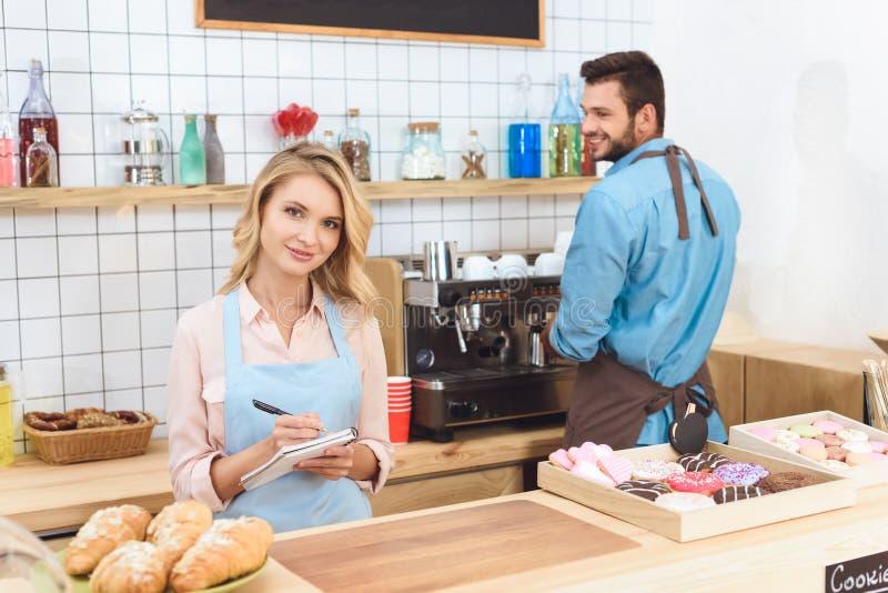 mooie jonge serveerster die nota's nemen en bij camera glimlachen terwijl barista het maken stock afbeelding