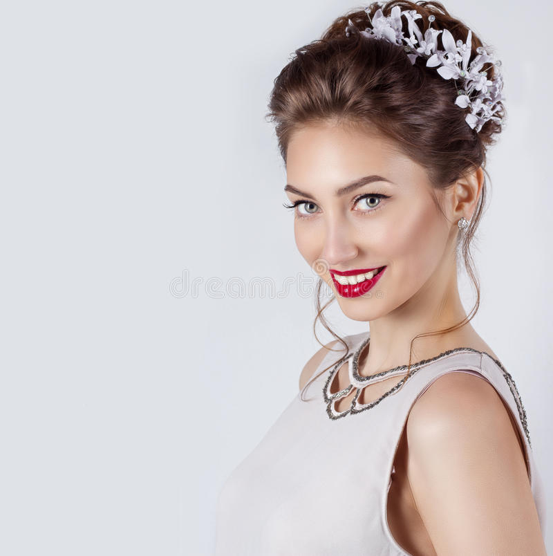 Mooie jonge sexy elegante gelukkige glimlachende vrouw met rode lippen, mooi modieus kapsel met witte bloemen in haar haar stock afbeelding