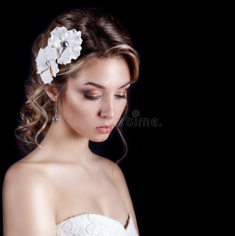 Mooie jonge sexy elegante gelukkige glimlachende vrouw met rode lippen, mooi modieus kapsel met witte bloemen in haar haar royalty-vrije stock afbeelding