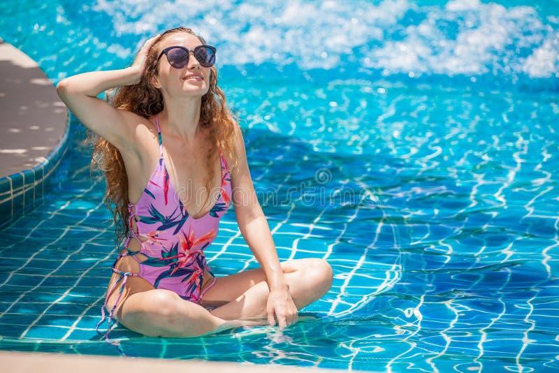 mooie Jonge sexy vrouw die bikini met zonnebril in zwembad dragen Mooi meisje in zwempak die en bij stellen ontspannen royalty-vrije stock fotografie