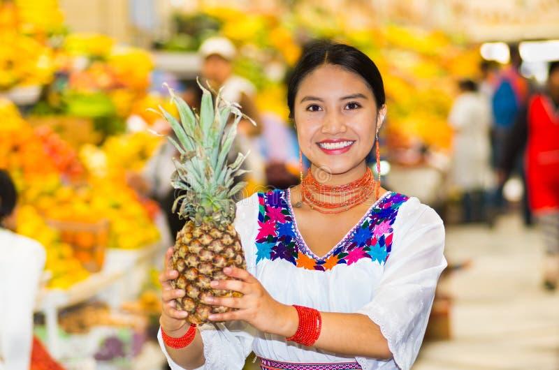 Mooie jonge Spaanse vrouw die het Andes traditionele blouse stellen voor de ananas van de cameraholding binnen fruitmarkt dragen stock afbeelding