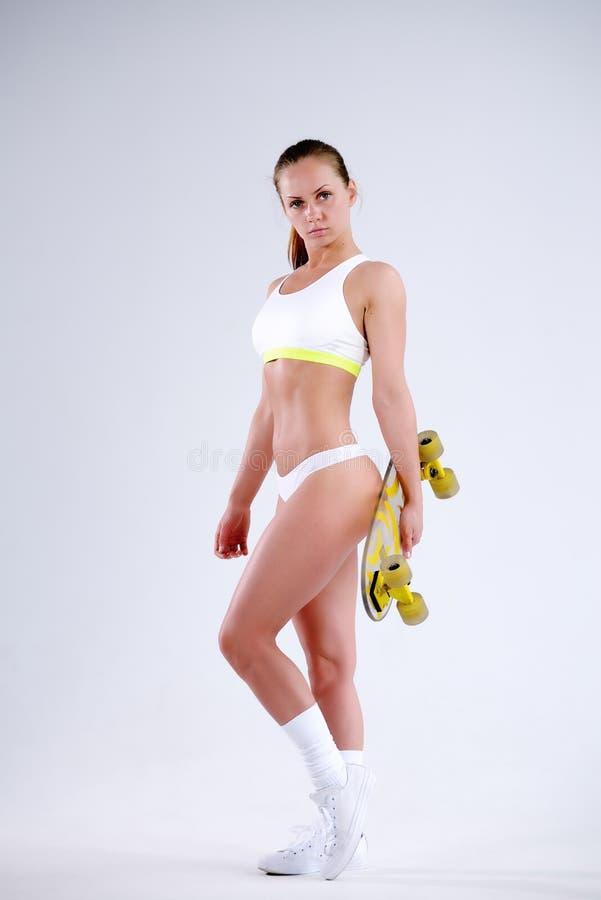 Mooie jonge sportenvrouw met skateboard in studio stock foto
