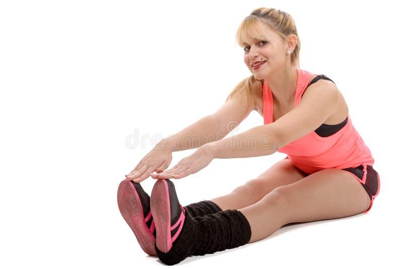 Mooie jonge sportvrouw die uitrekkende oefeningen doen stock afbeeldingen