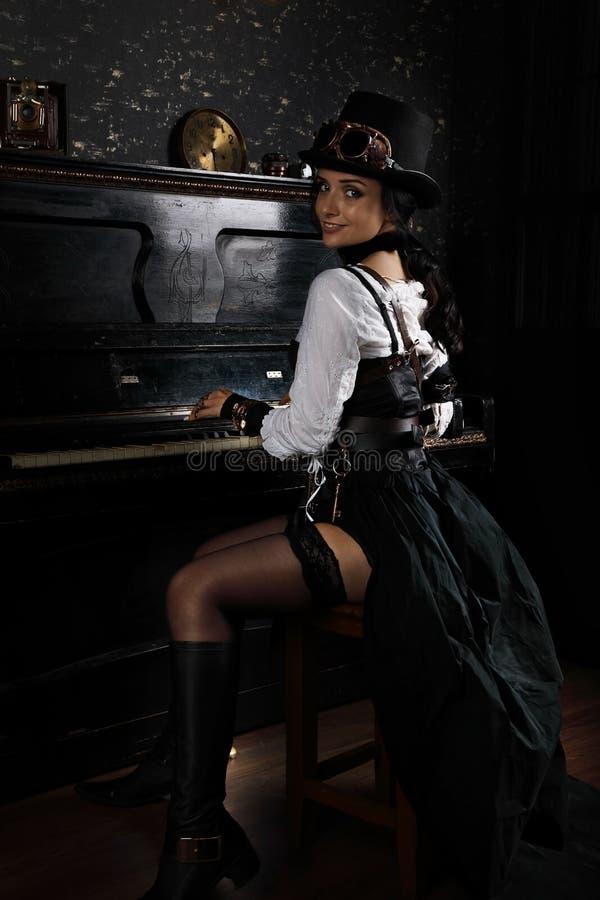 Mooie jonge steampunkvrouw die de piano spelen royalty-vrije stock fotografie