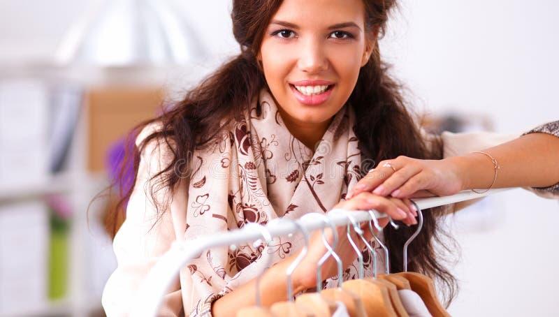 Download Mooie Jonge Stilistvrouw Dichtbij Rek Met Hangers Stock Foto - Afbeelding bestaande uit koper, kleren: 107704688