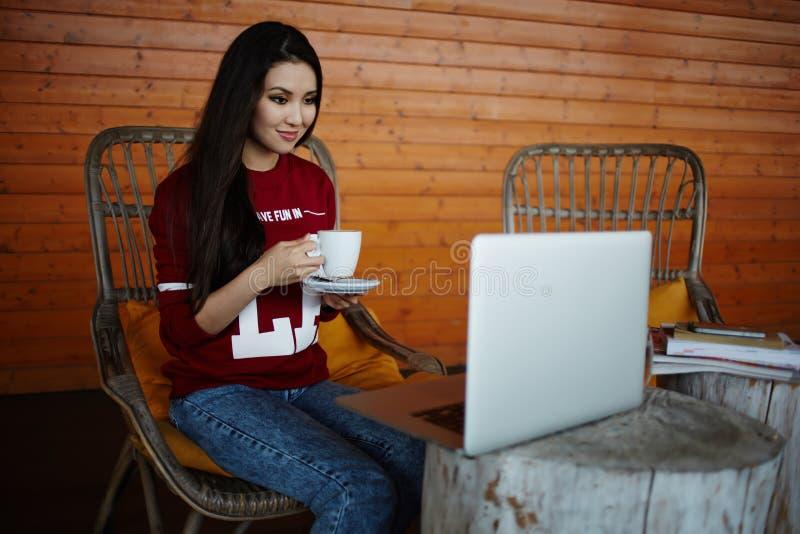 Mooie jonge student het drinken thee op de veranda royalty-vrije stock afbeelding