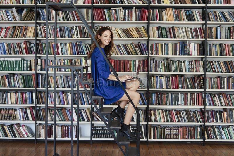 Mooie jonge studentzitting op treden in de bibliotheek, die aan laptop werken Vrouw die blauwe kleding, boekenrek dragen stock foto's
