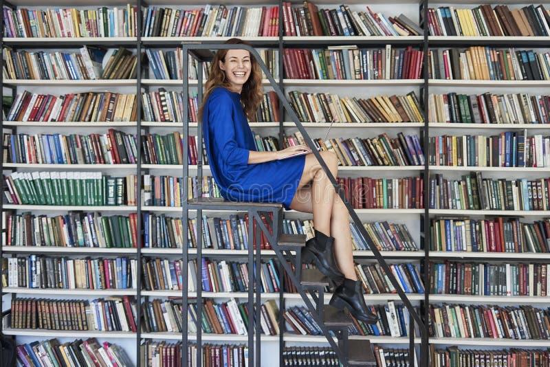 Mooie jonge studentzitting op treden in de bibliotheek, die aan laptop werken Vrouw die blauwe kleding, reusachtig boekenrek drag stock fotografie