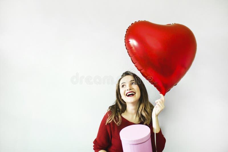 Mooie jonge van de het hartvorm van de vrouwenholding de luchtballon en giftdoos op een grijze achtergrond royalty-vrije stock foto's