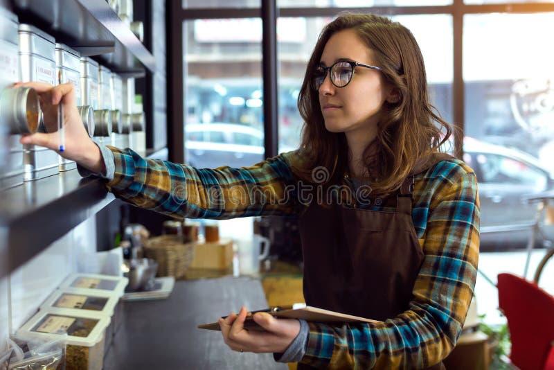 Mooie jonge verkoopster die inventaris in een detailhandel verkopende koffie doen stock fotografie