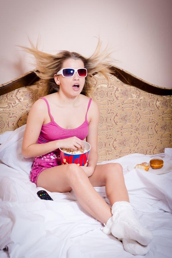 Mooie jonge verraste blonde vrouw die in roze kleurenpyjama's het letten op film in 3D glazen zitten en het eten van popcorn royalty-vrije stock afbeeldingen