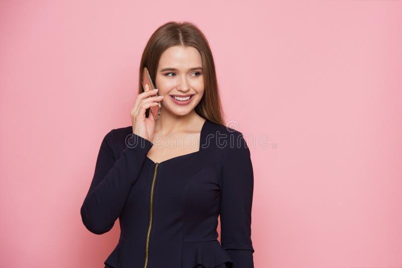 Mooie jonge volwassen bedrijfsvrouw die bij het mobiele telefoon glimlachen spreken die aan de kant op roze achtergrond kijken royalty-vrije stock foto's