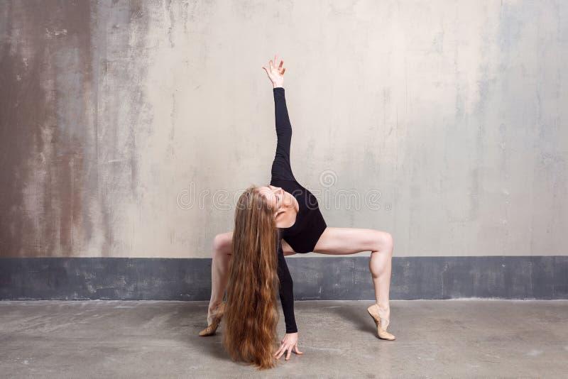Mooie jonge volwassen langharige vrouw die in studio dansen stock foto