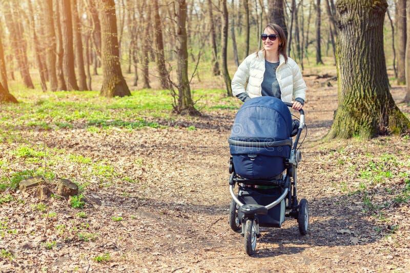 Mooie jonge volwassen vrouw die met baby in wandelwagen door bos lopen of park op heldere zonnige dag Gezonde levensstijl en stock afbeelding