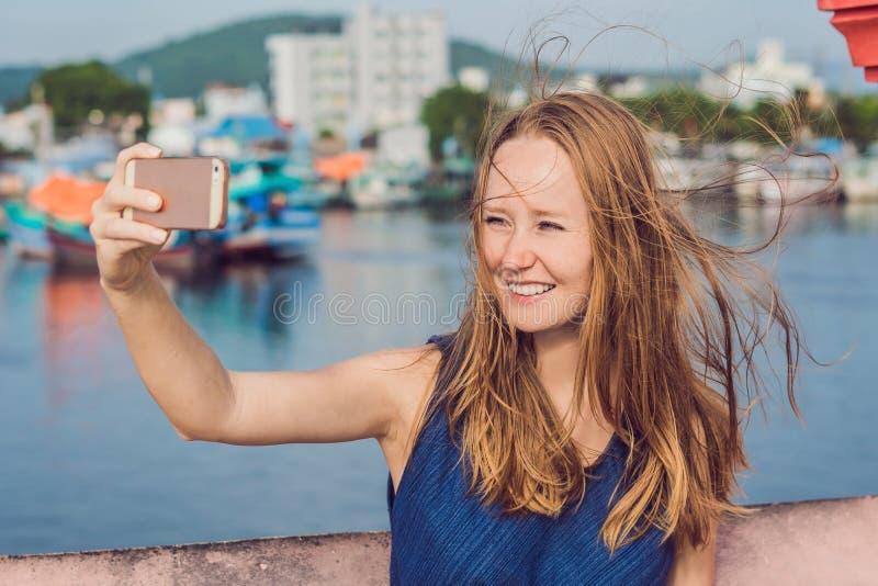 Mooie jonge vrolijke vrouw die een selfie nemen tegen backg stock fotografie