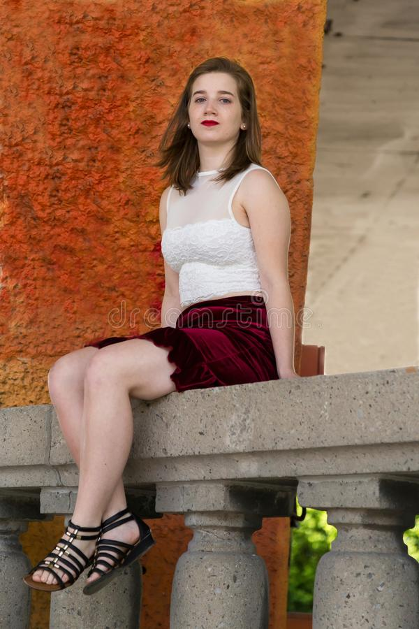 Mooie jonge vrouw in bebouwde witte hoogste en korte rode rokzitting op steenbalustrade stock fotografie