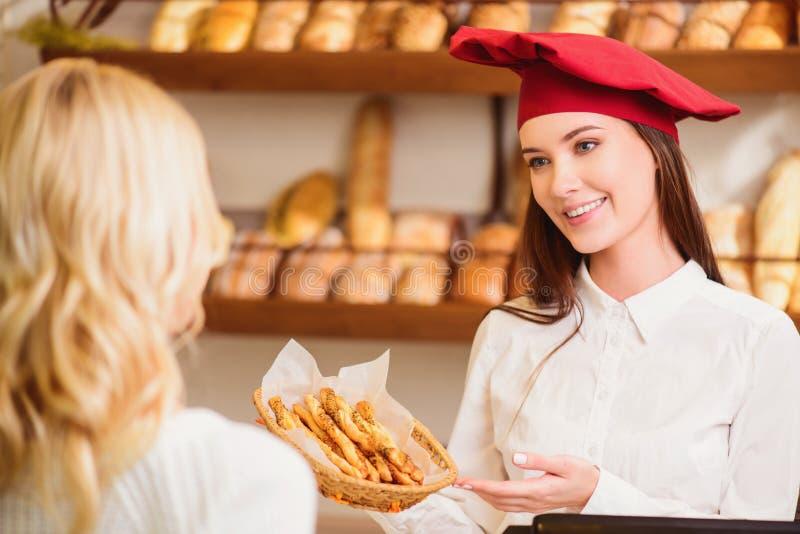 Mooie jonge vrouw bij bakkerswinkel stock afbeeldingen