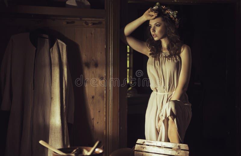 Mooie jonge vrouw bij een oud rustiek plattelandshuisje royalty-vrije stock afbeelding