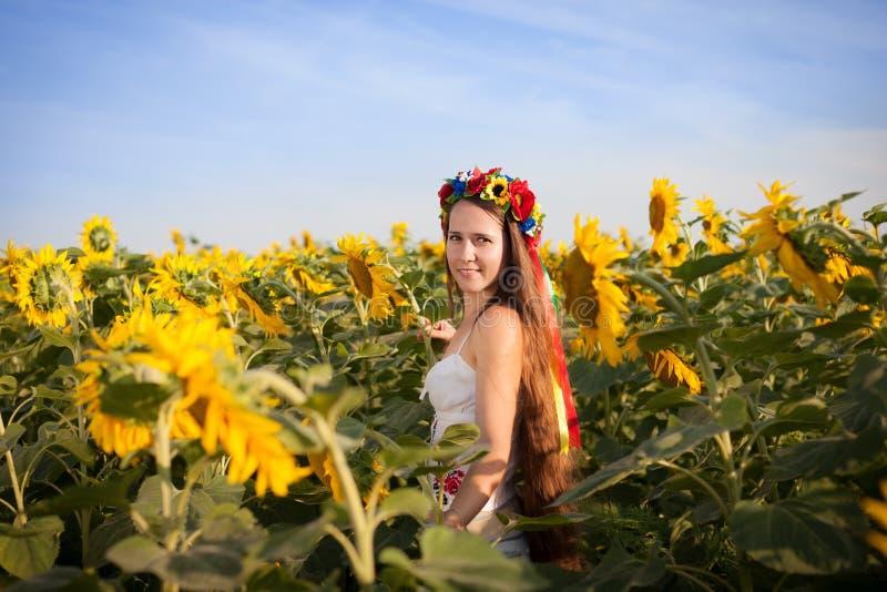 Mooie jonge vrouw bij zonnebloemgebied royalty-vrije stock afbeeldingen