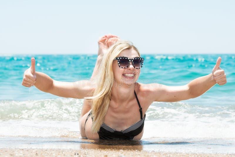 Mooie jonge vrouw in bikini die en op het strand liggen zonnen stock foto's