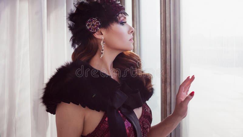 Mooie jonge vrouw binnen in een het silhouetkleding van Bourgondië dichtbij het venster, retro stijl stock afbeeldingen