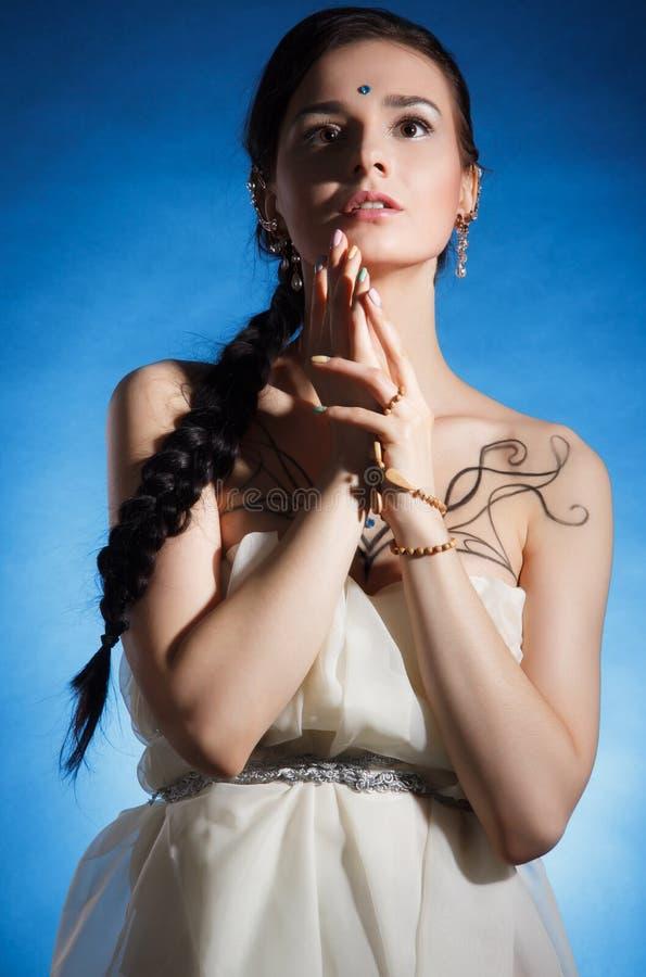 Mooie jonge vrouw binnen met een lange vlecht royalty-vrije stock afbeelding