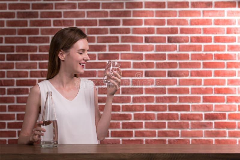 Mooie jonge vrouw in blije houding met fles en glas drinkwater royalty-vrije stock foto's
