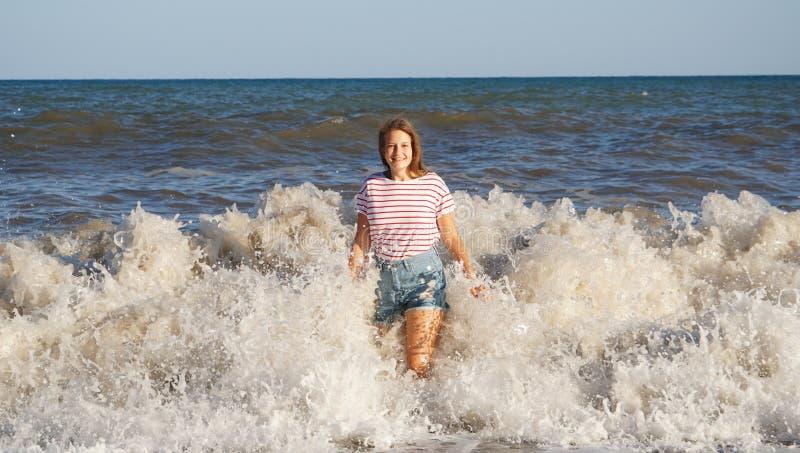 Mooie jonge vrouw in brandingsgolven op het strand royalty-vrije stock afbeelding