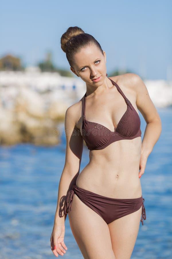 Mooie jonge vrouw in bruine bikini die op zee stellen stock foto's