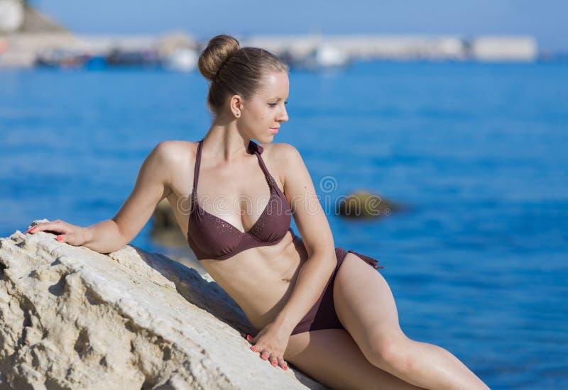 Mooie jonge vrouw in bruine bikini tegen overzees stock afbeelding