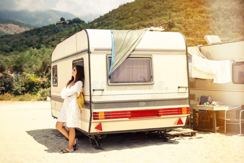 Mooie jonge vrouw buiten de kampeerautobestelwagen op een de zomerdag royalty-vrije stock foto's