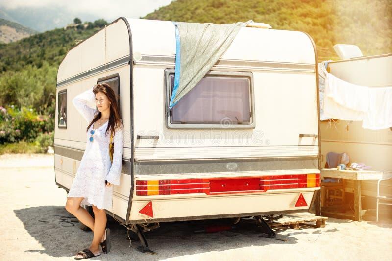 Mooie jonge vrouw buiten de kampeerautobestelwagen op een de zomerdag stock foto
